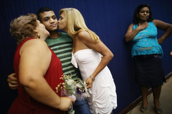 Couple Marcia (L) and Jaqueline kiss Marcia's son Gustavo while posing before marrying at what was billed as the world's largest communal gay wedding on December 8, 2013 in Rio de Janeiro, Brazil. 130 couples were married at the event which was held at the Court of Justice in downtown Rio. In May, Brazil became the third country in Latin America to effectively approve same-sex marriage via a court ruling, but a final law has yet to be passed. (Photo by Mario Tama/Getty Images)
