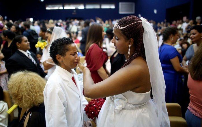 Newly married couple Joyce and Gabrieli (R) react at what was billed as the world's largest communal gay wedding on December 8, 2013 in Rio de Janeiro, Brazil. 130 couples were married at the event which was held at the Court of Justice in downtown Rio. In May, Brazil became the third country in Latin America to effectively approve same-sex marriage via a court ruling, but a final law has yet to be passed. (Photo by Mario Tama/Getty Images)