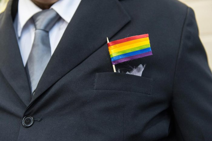 The father of a bride wears a rainbow flag during the wedding ceremony at the Court of Justice of the State of Rio de Janeiro in Rio de Janeiro, Brazil, on December 8, 2013. 130 gay couples are getting married in the first massive wedding ceremony since the first gay marriage in Rio de Janeiro in 2011. AFP PHOTO / YASUYOSHI CHIBA (Photo credit should read YASUYOSHI CHIBA/AFP/Getty Images)