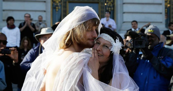 Gypsy Taub, right, embraces Jaymz Smith, left, following their nude wedding outside City Hall Thursday, Dec. 19, 2013, in San Francisco. Taub, the face and body of San Francisco's nude rights movement, tied the knot outside City Hall and was later cited and released by police. Taub, a mother of three who conducts nude interviews on public access TV, has been arrested repeatedly for violating the city's public nudity ban. (AP Photo/Eric Risberg)