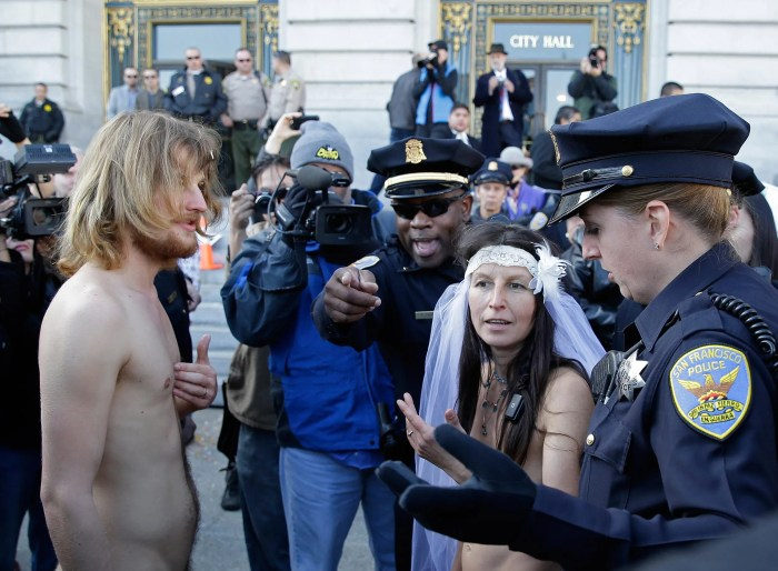 San Francisco police lead away Gypsy Taub, right, and Jaymz Smith, left, to a van after their nude wedding outside City Hall, Thursday, Dec. 19, 2013, in San Francisco. Taub, the face and body of San Francisco's nude rights movement, tied the knot outside City Hall and was later cited and released by police. Taub, a mother of three who conducts nude interviews on public access TV, has been arrested repeatedly for violating the city's public nudity ban. (AP Photo/Eric Risberg)