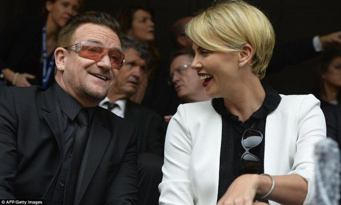 Stars: U2 singer Bono and South African actress Charlize Theron talking in the crowd at the ceremony