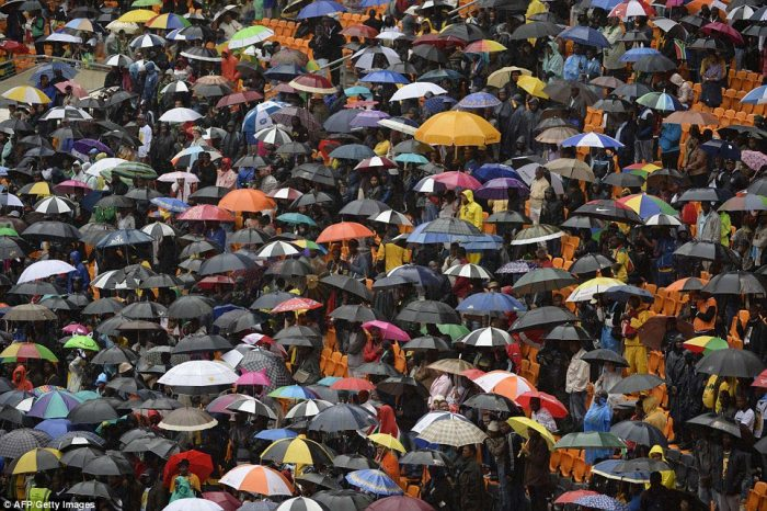 Umbrella weather: The ceremony started an hour late in the pouring rain to allow dignitaries and members of the public to file in to the arena