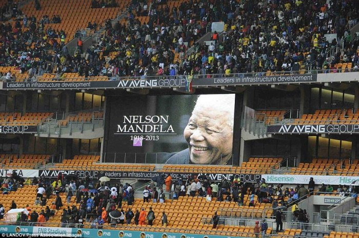 Respect: Nelson Mandela is shown on a giant screen inside the stadium as thousands of South Africans and global dignitaries file into the ground