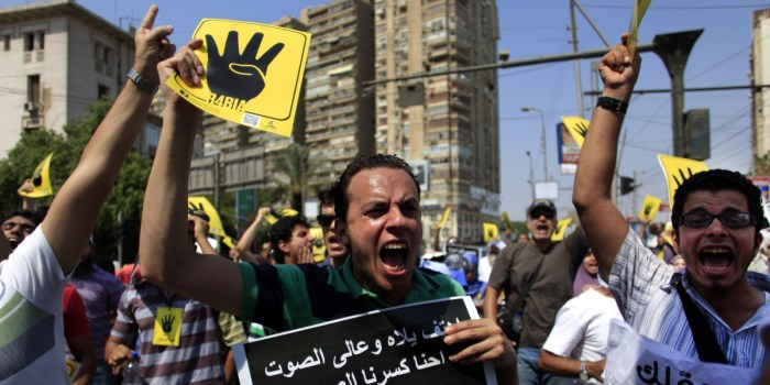 """Supporters of Egypt's ousted President Mohammed Morsi chant slogans and hold placards showing an open palm with four raised fingers, which has become a symbol of the Rabaah al-Adawiya mosque, where Morsi supporters had held a sit-in for weeks that was violently dispersed on Aug. during a protest in Cairo, Egypt, Friday, Sept. 6, 2013. Thousands of protesters flowed out of mosques on Friday in Muslim Brotherhood-led rallies against the military-backed government a day after a car bomb in the Egyptian capital marked a substantial escalation in Egypt's violent turmoil. Arabic writing on the black poster reads """" Chant loud we Brooke the voice with death."""" (Photo Credit: AP/Khalil Hamra)"""