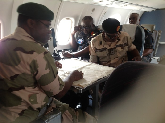 The Chief of Army Staff Lt Gen Kenneth Minima (left) and his Air Force Counterpart, Chief of Air Staff,  Air Marshal Adesola Amosu, (middle) aboard a Nigerian Airforce reconnoissance plane putting heads  together with maps embark patrol of the mission area.