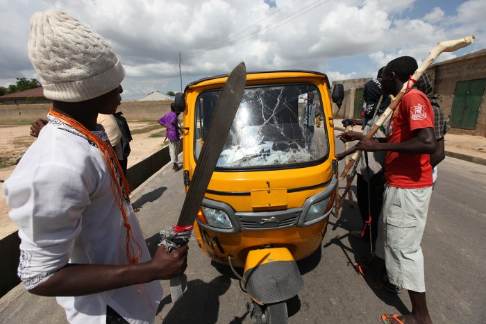 "In this photo taken Wednesday, Aug. 7, 2013. members of the  ""Civilian JTF ""  with cutlasses and clubs mount a check point on the street of Maiduguri,  Nigeria.  (Photo Credit: AP/Sunday Alamba)"