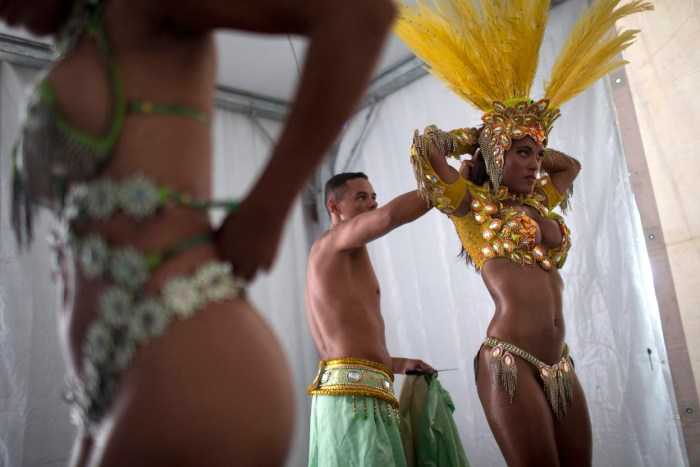 Samba dancer Diana Prado, right, in costume as she prepares for a carnival parade at central station in Rio de Janeiro. Though passistas are unquestionably the star attractions of the world's most iconic Carnival celebrations, they're not on the payroll of the samba school they represent. (AP Photo/Felipe Dana)