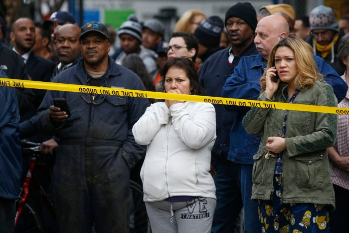Residents watch as firefighters work at the scene of a building collapse in New York, March 12, 2014. (Shannon Stapleton—Reuters)