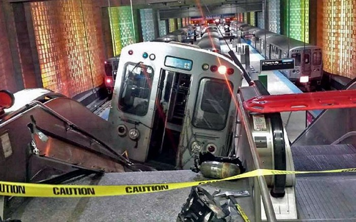 A Chicago Transit Authority train car rests on an escalator at the O'Hare Airport station after it derailed. More than 30 people were injured after the train 'climbed over the last stop, jumped up on the sidewalk and then went up the stairs and escalator,' according to Chicago Fire Commissioner Jose Santiago (Photo Credit: KENNETH WEBSTER/AP)