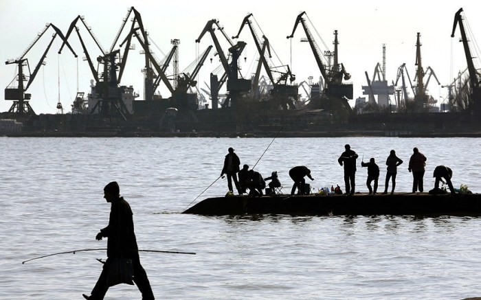 People fish on a pier at the port of Mariupol, located on the north of the Sea of Azov in eastern Ukraine. (Photo Credit: YANNIS BEHRAKIS/REUTERS)
