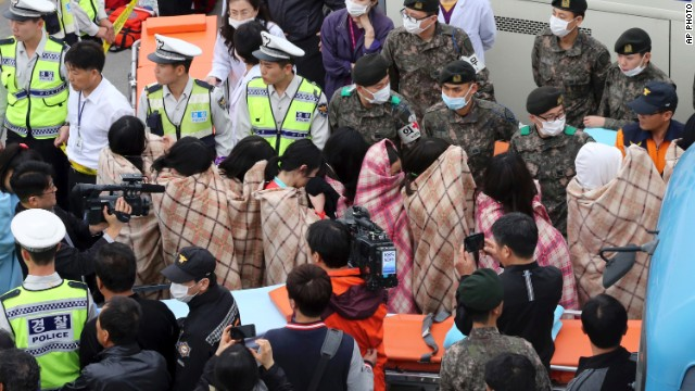 Rescued passengers are escorted by officials on their arrival at a port in Jindo, South Korea. (Photo: CNN)