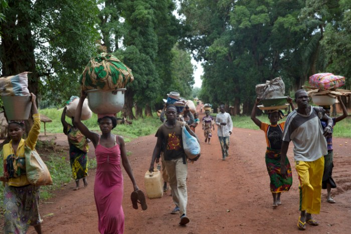 Grimari. Christians who took refugee at the Catholic mission of Grimari to flee the fighting between Seleka and Antibalakas, are fastly walking back  to their home to get food and belongings during a break of fighting, thanks to the arrival of some Sangaris renforts. Grimari is being attacked by Antibalakas for 2 days as it is the gate to the Ouaka region that is still controlled by ex Seleka fighters whose general Ali Mahamat Darrassa is relatively appreciated by both muslims and christians for having fought and expelled others Seleka who were installing terror among the city communities. Sangaris troops trust him, thinking he is the only way to keep Ouaka region out of violence. (Photo Credit: William Daniels/Panos)