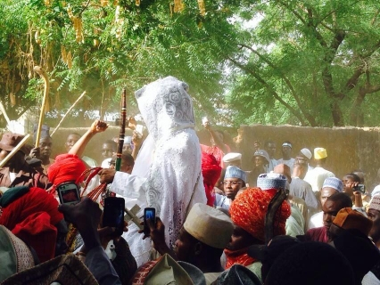 The Emir riding into his palace surrounded by supporters