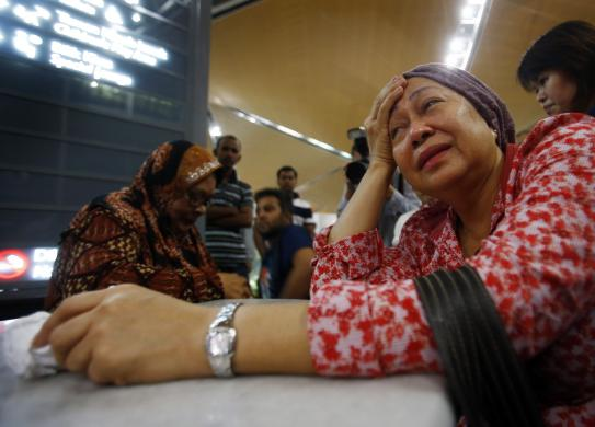 A woman (front), who said she believed her sister was on Malaysia Airlines flight MH-17, cries as she waits for more information about the crashed plane, at Kuala Lumpur International Airport in Sepang, July 18, 2014.     (Photo Credit: REUTERS/Samsul Said)