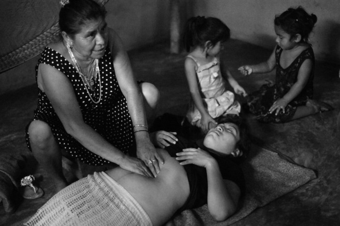 Traditional Mayan midwife Elsa Gonzalez Ayala shows CASA Midwifery School students how to perform a traditional Mayan massage used to shrink a woman's uterus and reduce post-partum bleeding - on Nelsi Marvella Tuk Balam.CASA Midwifery School students traveled to the rural village of Chunhuhub to learn traditional methods from traditional Mayan midwives and to teach them contemporary practices in exchange. (Photo Credit: Alice Proujansky)