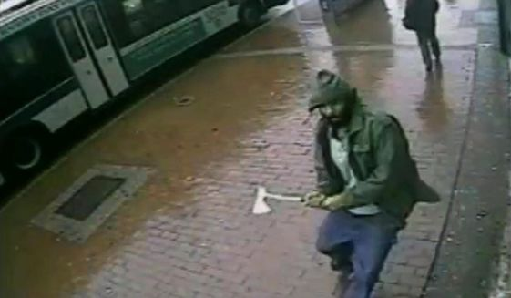 In this frame grab taken from video provided by the New York Police Department, an unidentified man approaches New York City police officers with a hatchet, Thursday, Oct. 23, 2014, in the Queens borough of New York. The man injured two with the hatchet before the other officers shot and killed him, police said. A bystander was wounded in the gunfire. Investigators were still trying to confirm the identity of the assailant and determine a motive. (Photo Credit: AP/New York Police Department)