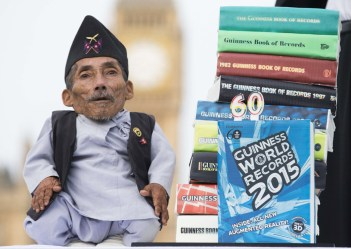Bahadur Dangi, from Nepal, the shortest adult to have ever been verified by Guinness World Records, is pictured next to a stack of books during a photocall in central London, on November 13, 2014, to mark Guinness World Records Day. Chandra Dangi, measures a tiny 21.5in (0.54m). (Photo Credit: Andrew Cowie/AFP/Getty Images)
