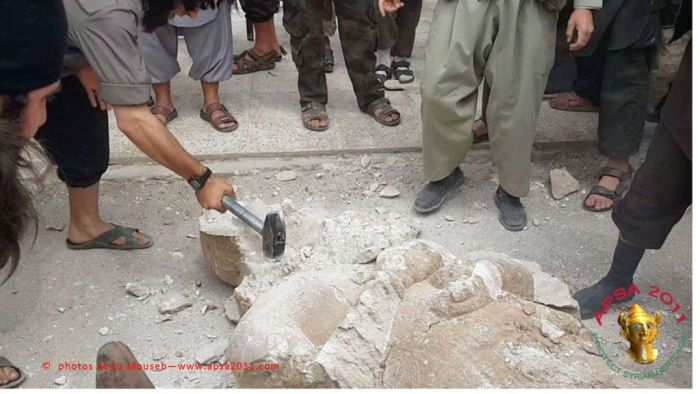 Members of the Islamic State of Iraq and the Levant smash an Assyrian statue. (photo courtesy of APSA/Abou Mouseb) Read more: Radical Islamists take hammer to Syrian artifacts | The Times of Israel (Photo Credit: The Times of Israel)