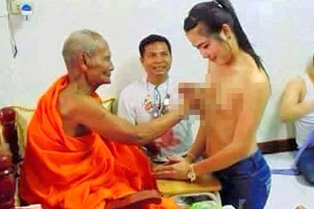 Unidentified Buddhist Monk pictured fondling the breasts of a topless woman in Thailand. (Photo Credit: CEN)
