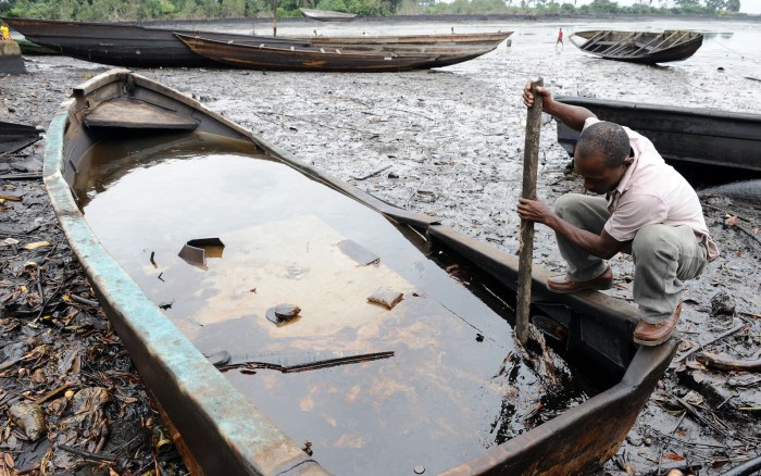 FILE: An indigene of Bodo, Ogoniland region in Rivers State, tries to separate with a stick the crude oil from water in a boat at the Bodo waterways polluted by oil spills attributed to Shell equipment failure August 11, 2011.           (Photo Credit: AFP/Pius Ekpei)