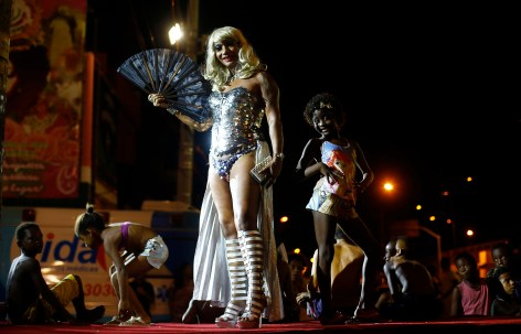 A girl poses next to a reveller at the entrance of the Glam Gay pre-carnival Ball, in Mangueira samba school in Rio de Janeiro February 11, 2015.The Rio de Janeiro Carnival will be held from February 13 to 17. Picture taken February 11, 2015. (REUTERS/Ricardo Moraes)