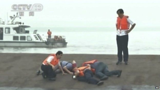 Rescuers knocking on the capsized hull to make contact with those inside the ship  on of the rescued 15 survivors being pulled out by rescuers (Credit: BBC/CCTV)