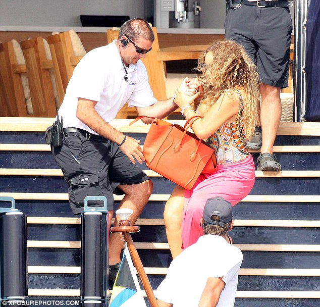 Super stylish: Mariah did manage to fall in style, wearing a provocative swimsuit with a plunging neckline