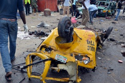 A man walk past an auto-rickshaw damaged following an Improvised Explosive Devices (IED) at Gomboru market in Maiduguri, Borno State in northeastern Nigeria on July 31, 2015 detonated by a female suicide bomber who arrived on a taxi tricycle killings at least eight people and several other. A female suicide bomber blew herself up at a big market in the northeast Nigerian city of Maiduguri, a vigilante and a witness said. (Photo Credit: AFP PHOTO/STRINGER)
