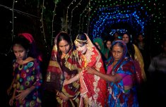 15 year old Nasoin Akhter is led by relatives to a car that will take her to her new home on the day of her wedding to a 32 year old man, August 20, 2015 in Manikganj, Bangladesh. (Photo Credit: Allison Joyce/Getty Images)