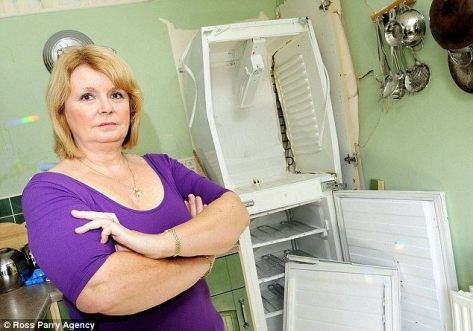 A British woman stands beside her fridge that exploded in her kitchen