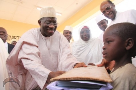 Former President Goodluck Jonathan presents books and school materials to a street beggar at the launch of one of his Almajirai Kano