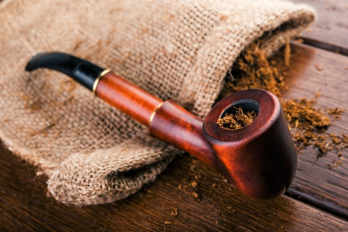 Smoking pipe and tobacco on brawn wooden table. how