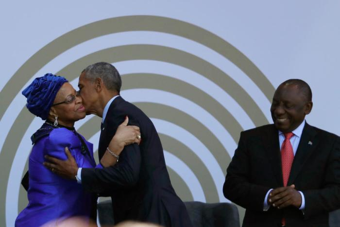 Former US president Barack Obama, centre, greets Nelson Mandela's widow, Graca Machel (Themba Hadebe/AP)