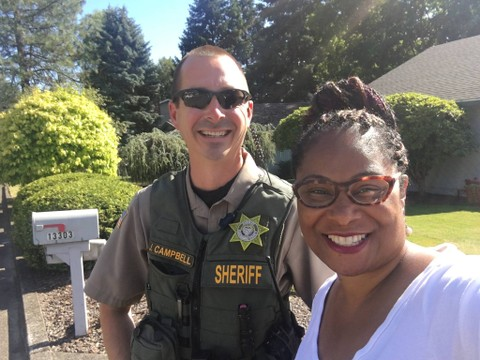 Oregon state Rep. Janelle Bynum takes a photo with a Clackamas County deputy who responded to a 911 call from one of her constituents who thought she looked suspicious as she was canvassing in a Clackamas neighborhood on July 3, 2018. (Courtesy of Janelle Bynum)
