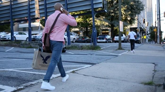 man shopping walking phone