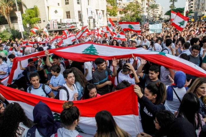 Lebanese students wave national flags as they gather in an a