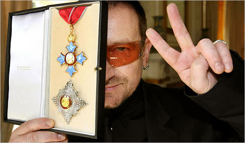 """Speaking of mixing entertainment with high power, here's Bono showing off an award he received from Queen Elizabeth II – the same queen that gave an award to mass abuser Jimmy Savile. Let's call this the occult elite award. Note the underlying """"one eye"""" theme in the photo. Click to enlarge"""