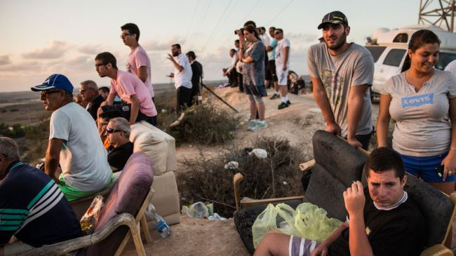 Israelis sit on a hill to watch the Tel Aviv regime's airstrikes on the besieged Gaza Strip, July 2014. Click to enlarge