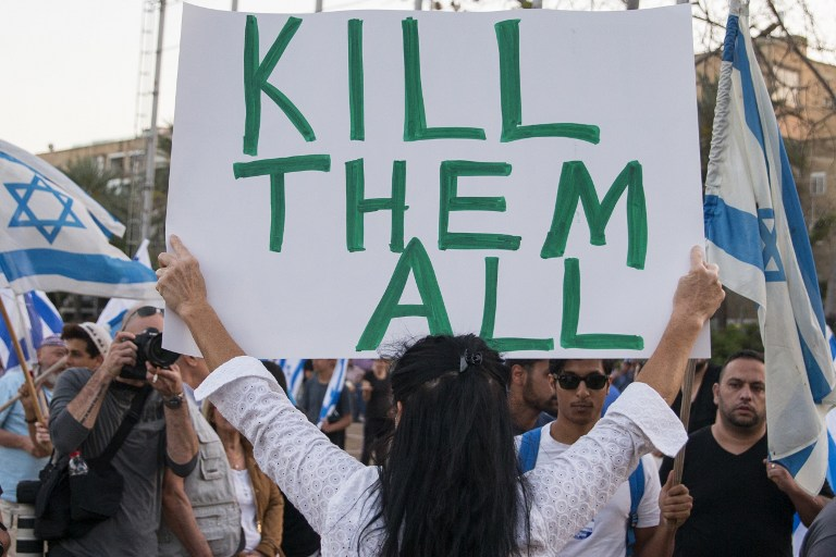Israeli citizens hold Israeli flags and banners during a rally in Tel Aviv on April 19, 2016 to support Elor Azria, an Israeli soldier recently charged with manslaughter after shooting a prone and wounded Palestinian assailant in the head. The rally, attended by an estimated 5,000 people, was a source of controversy in Israel where the top brass have condemned Azria's actions while far-right supporters and politicians urged his release. / AFP PHOTO / JACK GUEZ