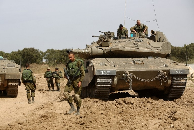 Israeli soldiers stand guard with their tank along the border between Israel and the Gaza Strip near the southern Israeli Kibbutz of Nahal Oz on May 4, 2016. Click to enlarge