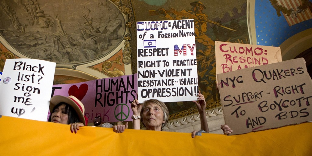 Demonstrators hold signs during a rally in the War Room at the New York state Capitol on June 15, 2016, in Albany, N.Y.