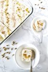 Kulfi in a rectangular glass dish with individual servings in two white bowls and stainless steel teaspoons.