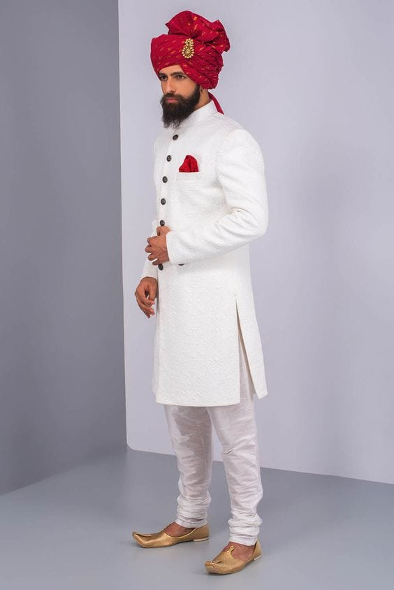 simple white sherwani and pajama with golden mojari for groom