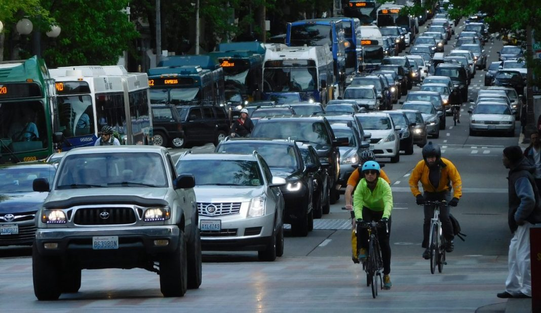 A snarl of car traffic on 4th Avenue with transit and people biking on the margins. (Photo by Scott Bonjukian)