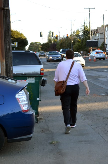 A man walks between parked cars and oncoming traffic on Greenwood Avenue N. (photo by author)