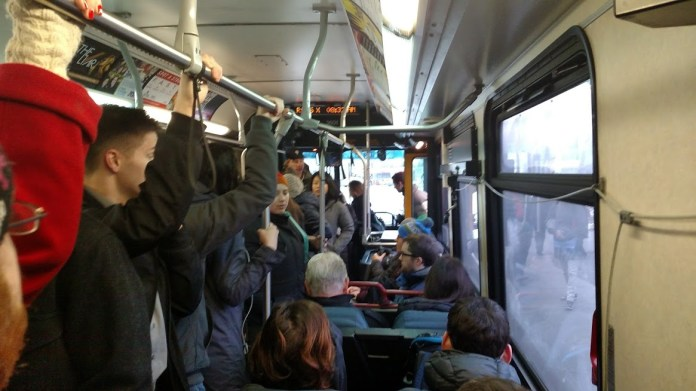 People hold on to the overhead handle on a standing room bus headed down Aurora.