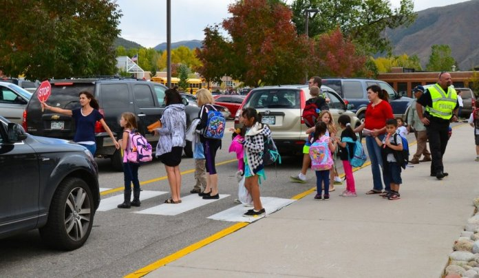 A school crosswalk busy with students and parents in a sea of cars.