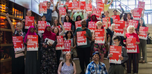 Advocates hold red signs backing rent control and housing the homeless.