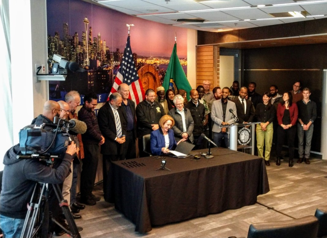 Mayor Jenny Durkan signs the Fare Share Plan into law at city hall. (Photo by Doug Trumm)